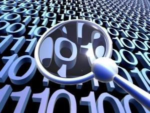 Magnifying glass looking at binary code